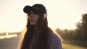 Πορτρέτο κινηματογραφήσεων σε πρώτο πλάνο ενός κοκκινομάλλους κοριτσιού με να διαπερνήσει νέα γυναίκα που ακούει τη μουσική στα α απόθεμα βίντεο