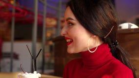 Πορτρέτο κινηματογραφήσεων σε πρώτο πλάνο ενός κοριτσιού σε έναν καφέ με ένα κοκτέιλ ή latte υπό εξέταση απόθεμα βίντεο