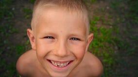 Πορτρέτο κινηματογραφήσεων σε πρώτο πλάνο ενός μπλε-eyed μικρού παιδιού που εξετάζει και που χαμογελά άμεσα τη κάμερα, ένα να δια φιλμ μικρού μήκους