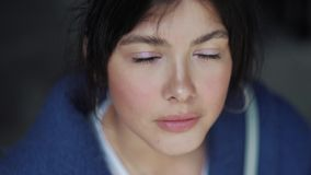 Πορτρέτο κινηματογραφήσεων σε πρώτο πλάνο ενός νέου κοριτσιού με τη ζάλη των μπλε-καστανών ματιών απόθεμα βίντεο