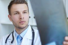 Πορτρέτο κινηματογραφήσεων σε πρώτο πλάνο ενός νέου όμορφου αρσενικού γιατρού που εξετάζει την ακτίνα X στοκ εικόνα