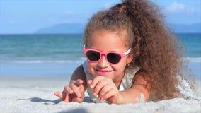 Πορτρέτο κινηματογραφήσεων σε πρώτο πλάνο ενός όμορφου μικρού κοριτσιού στα ρόδινα γυαλιά, χαριτωμένο χαμόγελο που εξετάζει τη κά φιλμ μικρού μήκους