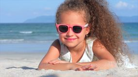 Πορτρέτο κινηματογραφήσεων σε πρώτο πλάνο ενός όμορφου μικρού κοριτσιού στα ρόδινα γυαλιά, χαριτωμένο χαμόγελο που εξετάζει τη κά απόθεμα βίντεο