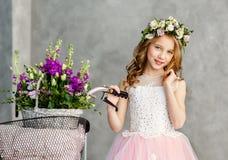 Πορτρέτο κινηματογραφήσεων σε πρώτο πλάνο ενός όμορφου χαριτωμένου μικρού κοριτσιού σε ένα στεφάνι των φρέσκων λουλουδιών στο κεφ στοκ εικόνα με δικαίωμα ελεύθερης χρήσης