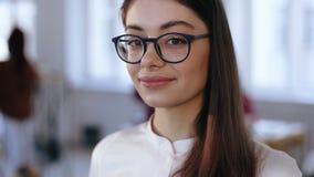 Πορτρέτο κινηματογραφήσεων σε πρώτο πλάνο, ευτυχής νέα επαγγελματική επιχειρησιακή γυναίκα σχεδίου brunette eyeglasses που χαμογε απόθεμα βίντεο