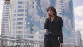 Πορτρέτο κινηματογραφήσεων σε πρώτο πλάνο μιας γυναίκας σε ένα επίσημο κοστούμι Νέα επιχειρησιακή γυναίκα που μιλά σε ένα smartph φιλμ μικρού μήκους