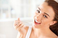 Πορτρέτο κινηματογραφήσεων σε πρώτο πλάνο μιας ελκυστικής νέας γυναίκας που τρώει το γιαούρτι Στοκ Εικόνες