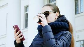Πορτρέτο κινηματογραφήσεων σε πρώτο πλάνο μιας νέας γυναίκας στα γυαλιά που πίνουν τον καφέ που χρησιμοποιεί το έξυπνο τηλέφωνο σ φιλμ μικρού μήκους