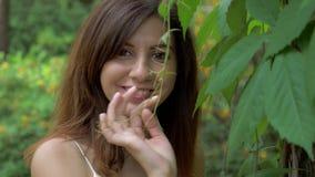 Πορτρέτο κινηματογραφήσεων σε πρώτο πλάνο μιας νέας όμορφης γυναίκας που εξετάζει τη κάμερα και το χαμόγελο απόθεμα βίντεο