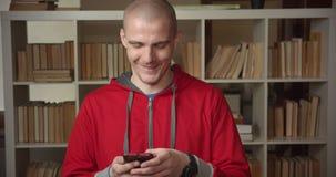 Πορτρέτο κινηματογραφήσεων σε πρώτο πλάνο νέο ελκυστικό καυκάσιο ανδρών σπουδαστών στο τηλέφωνο στη βιβλιοθήκη κολλεγίων στο εσωτ φιλμ μικρού μήκους
