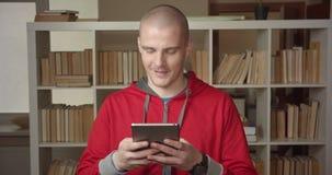 Πορτρέτο κινηματογραφήσεων σε πρώτο πλάνο νέο ελκυστικό καυκάσιο ανδρών σπουδαστών στην ταμπλέτα στη βιβλιοθήκη κολλεγίων στο εσω απόθεμα βίντεο