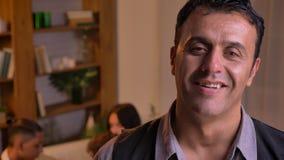 Πορτρέτο κινηματογραφήσεων σε πρώτο πλάνο της αραβικής προσοχής ατόμων στη κάμερα με το ευχάριστο χαμόγελο που στέκεται στο καθισ φιλμ μικρού μήκους