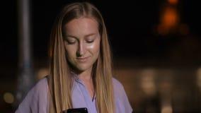 Πορτρέτο κινηματογραφήσεων σε πρώτο πλάνο της γυναίκας που χρησιμοποιεί το κινητό τηλέφωνο τη νύχτα απόθεμα βίντεο