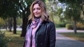 Πορτρέτο κινηματογραφήσεων σε πρώτο πλάνο της ελκυστικής νέας γυναίκας στο πάρκο φθινοπώρου κορίτσι στο σακάκι και το μαντίλι απόθεμα βίντεο