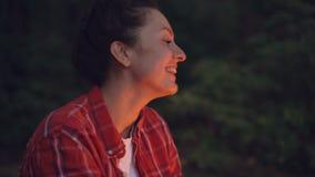 Πορτρέτο κινηματογραφήσεων σε πρώτο πλάνο της ελκυστικής νέας συνεδρίασης τουριστών γυναικών κοντά στα τραγούδια πυρών προσκόπων  φιλμ μικρού μήκους