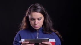 Πορτρέτο κινηματογραφήσεων σε πρώτο πλάνο της ενήλικης ελκυστικής καυκάσιας θηλυκής δακτυλογράφησης στην ταμπλέτα με το υπόβαθρο  απόθεμα βίντεο