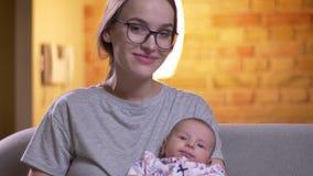 Πορτρέτο κινηματογραφήσεων σε πρώτο πλάνο της μητέρας που αγκαλιάζει με τη χαριτωμένη νεογέννητη κόρη της να προσέξει σοβαρά στη  φιλμ μικρού μήκους