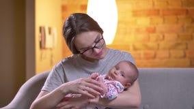Πορτρέτο κινηματογραφήσεων σε πρώτο πλάνο της μητέρας που διασκεδάζει τη χαριτωμένη νεογέννητη κόρη της στο καθιστικό απόθεμα βίντεο