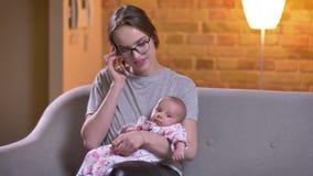 Πορτρέτο κινηματογραφήσεων σε πρώτο πλάνο της μητέρας που μιλά στο smartphone και που κρατά τη χαριτωμένη κόρη της στο καθιστικό απόθεμα βίντεο