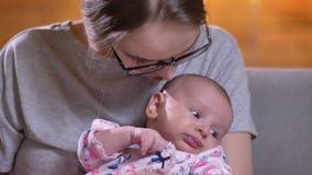 Πορτρέτο κινηματογραφήσεων σε πρώτο πλάνο της μητέρας που φιλά τη χαριτωμένη και όμορφη νεογέννητη κόρη της στο καθιστικό απόθεμα βίντεο