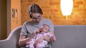 Πορτρέτο κινηματογραφήσεων σε πρώτο πλάνο της μητέρας που χαϊδεύει τη χαριτωμένη νεογέννητη κόρη της στο καθιστικό απόθεμα βίντεο