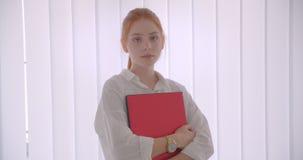 Πορτρέτο κινηματογραφήσεων σε πρώτο πλάνο της νέας αρκετά καυκάσιας redhead επιχειρηματία που κρατά το lap-top εξετάζοντας τη κάμ απόθεμα βίντεο