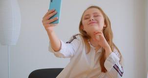Πορτρέτο κινηματογραφήσεων σε πρώτο πλάνο της νέας αρκετά καυκάσιας λήψης κοριτσιών selfies στο τηλέφωνο που θέτει τη συνεδρίαση  φιλμ μικρού μήκους