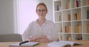Πορτρέτο κινηματογραφήσεων σε πρώτο πλάνο της νέας αρκετά redhead γυναίκας σπουδαστή στα γυαλιά που εξετάζει τη κάμερα που χαμογε φιλμ μικρού μήκους