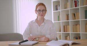 Πορτρέτο κινηματογραφήσεων σε πρώτο πλάνο της νέας αρκετά redhead γυναίκας σπουδαστή που καθορίζει τα γυαλιά της και που εξετάζει φιλμ μικρού μήκους
