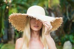 Πορτρέτο κινηματογραφήσεων σε πρώτο πλάνο της νέας γυναίκας στο μεγάλο καπέλο αχύρου, όμορφο θηλυκό που απολαμβάνει τον τροπικό η στοκ εικόνες
