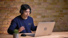Πορτρέτο κινηματογραφήσεων σε πρώτο πλάνο της νέας ελκυστικής κορεατικής τοποθέτησης ανδρών σπουδαστών στα ακουστικά και της κατο απόθεμα βίντεο