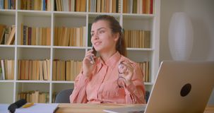 Πορτρέτο κινηματογραφήσεων σε πρώτο πλάνο της νέας ελκυστικής επιχειρηματία που μιλά άνετα στο τηλέφωνο που κρατά eyeglasses της  φιλμ μικρού μήκους