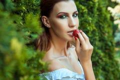 Πορτρέτο κινηματογραφήσεων σε πρώτο πλάνο της νέας ενήλικης γυναίκας που τρώει το κόκκινο γλυκό strawberr στοκ εικόνες
