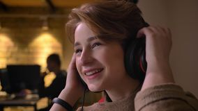 Πορτρέτο κινηματογραφήσεων σε πρώτο πλάνο της νέας με κοντά μαλλιά γυναίκας που αναβάλλει τα ακουστικά της και ευτυχώς που καλωσο απόθεμα βίντεο