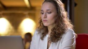 Πορτρέτο κινηματογραφήσεων σε πρώτο πλάνο της νέας σγουρός-μαλλιαρής γυναίκας που εργάζεται με το lap-top και που χαμογελά προσεκ απόθεμα βίντεο
