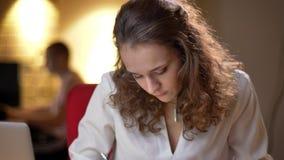Πορτρέτο κινηματογραφήσεων σε πρώτο πλάνο της νέας σγουρός-μαλλιαρής γυναίκας που γράφει στο σημειωματάριο και που χαμογελά προσε απόθεμα βίντεο