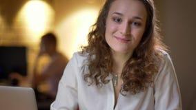 Πορτρέτο κινηματογραφήσεων σε πρώτο πλάνο της νέας σγουρός-μαλλιαρής γυναίκας που χαμογελά ευχάριστα στη κάμερα στην αρχή φιλμ μικρού μήκους