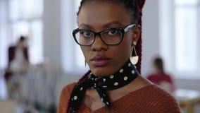 Πορτρέτο κινηματογραφήσεων σε πρώτο πλάνο της νέας όμορφης σοβαρής μαύρης επιχειρησιακής γυναίκας eyeglasses που εξετάζει τη κάμε φιλμ μικρού μήκους