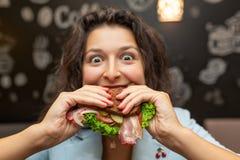 Πορτρέτο κινηματογραφήσεων σε πρώτο πλάνο της πεινασμένης νέας καυκάσιας γυναίκας, σάντουιτς δαγκωμάτων στοκ εικόνα με δικαίωμα ελεύθερης χρήσης