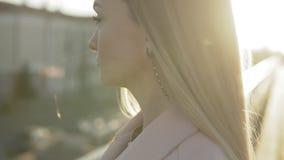 Πορτρέτο κινηματογραφήσεων σε πρώτο πλάνο της όμορφης γυναίκας με το μακρυμάλλες χαμόγελο υπαίθρια στην ανατολή απόθεμα βίντεο
