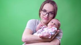 Πορτρέτο κινηματογραφήσεων σε πρώτο πλάνο της όμορφης μητέρας που θέτει και που κρατά τη χαριτωμένη και αρκετά νεογέννητη κόρη τη απόθεμα βίντεο