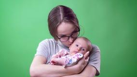 Πορτρέτο κινηματογραφήσεων σε πρώτο πλάνο της όμορφης μητέρας που θέτει τη χαριτωμένη νεογέννητη κόρη της που χασμουρητά prettily απόθεμα βίντεο