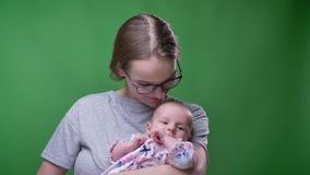 Πορτρέτο κινηματογραφήσεων σε πρώτο πλάνο της όμορφης μητέρας που φιλά τη χαριτωμένη και όμορφη νεογέννητη κόρη της στο πράσινο υ φιλμ μικρού μήκους