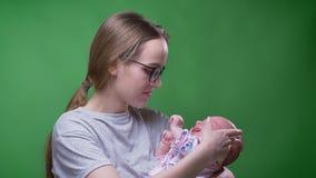 Πορτρέτο κινηματογραφήσεων σε πρώτο πλάνο της όμορφης μητέρας που κρατά και που φιλά τη χαριτωμένη και όμορφη νεογέννητη κόρη της απόθεμα βίντεο