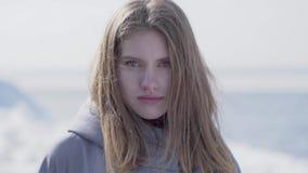 Πορτρέτο κινηματογραφήσεων σε πρώτο πλάνο της όμορφης νέας ξανθής γυναίκας με μακρυμάλλη και τα μπλε μάτια που κοιτάζει στη κάμερ απόθεμα βίντεο