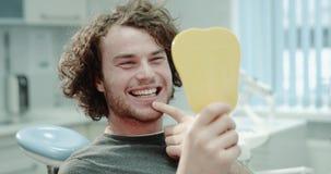 Πορτρέτο κινηματογραφήσεων σε πρώτο πλάνο του ασθενή με τα τέλεια δόντια μετά από μια επίσκεψη στον οδοντίατρό του, αυτός που κοι απόθεμα βίντεο