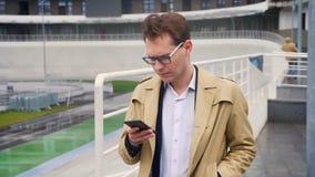 Πορτρέτο κινηματογραφήσεων σε πρώτο πλάνο του ελκυστικού καυκάσιου ατόμου που κοιτάζει βιαστικά στο τηλέφωνο και έπειτα που εξετά φιλμ μικρού μήκους