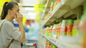 Πορτρέτο κινηματογραφήσεων σε πρώτο πλάνο του ελκυστικού νέου κοριτσιού που επιλέγει το χυμό στην υπεραγορά που στέκεται κοντά στ φιλμ μικρού μήκους