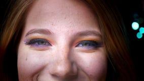 Πορτρέτο κινηματογραφήσεων σε πρώτο πλάνο του ελκυστικού ξανθού θηλυκού που χαμογελά στη κάμερα με τη ζωηρόχρωμη σύνθεση ματιών σ φιλμ μικρού μήκους
