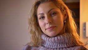 Πορτρέτο κινηματογραφήσεων σε πρώτο πλάνο του ενήλικου αρκετά καυκάσιου ξανθού θηλυκού που εξετάζει τη κάμερα και που χαμογελά χα φιλμ μικρού μήκους